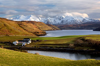 Gesto Farm and Snow on the Cuillin. Loch Harport. Isle of Skye. Scotland.